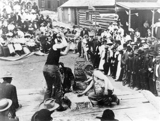 View of a mining competition at Fifth and Harrison Streets, Leadville, Colorado; shows miners on a platform during a double jack contest. The man who holds the sledge hammer is possibly Fred C. Dopp ca. 1901-1910. Courtesy Denver Public Library